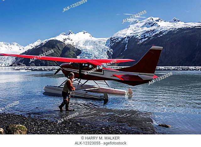 Pilot maneuvers a Cessna 206 floatplane; Coxe Glacier in Barry Arm of Prince William Sound; Southcentral Alaska; tidewater glacier