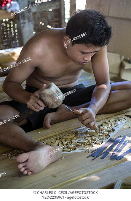 Bali, Indonesia. Woodcarver Carving Design into Door Frame in Woodworker's Workshop