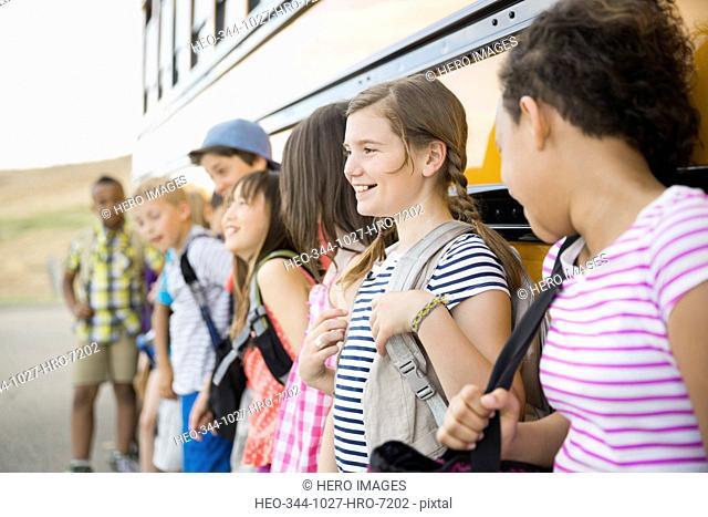 Schoolchildren standing against bus during field trip