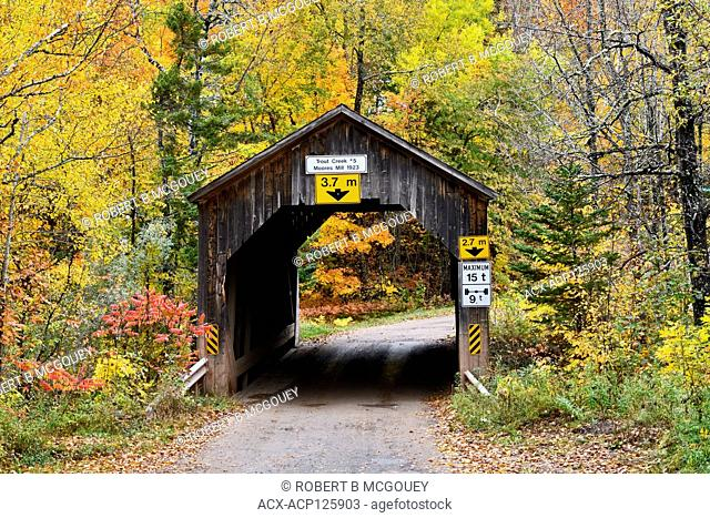 An autumn landscape image of an iconic covered bridge crossing Trout Creek on a rural gravel road near Sussex New Brunswick Canada