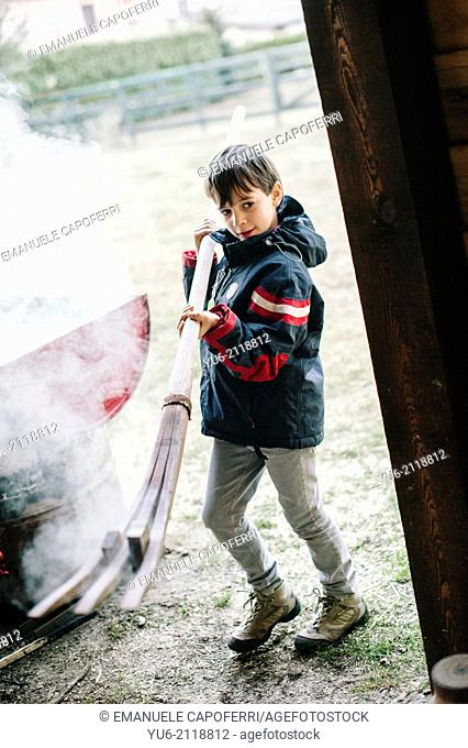 Child draws a strip of wood by boiling, Ispra, Varese, Italy