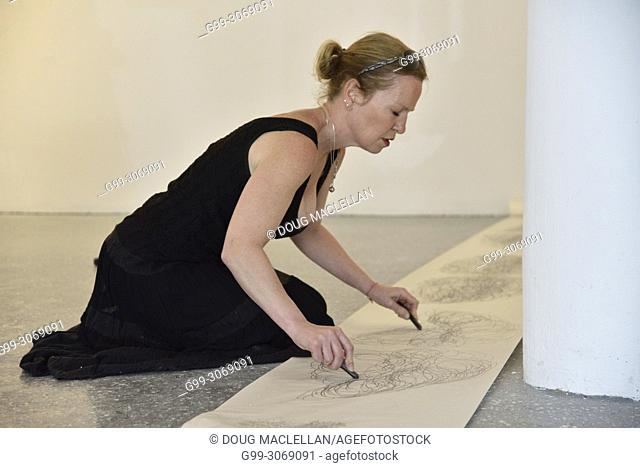 A woman artist wearing a black dress and on her knees draws with both hands as she creates a performance art work at an artist run gallery in Windsor, Canada