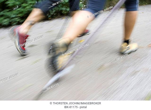 Legs of two nordic walker with yellow and red gym shoes and sticks in the English Garden in Munich