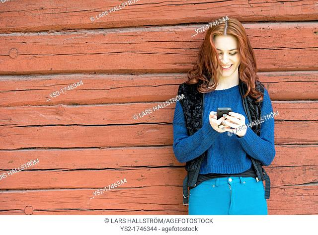 Beatiful young woman with red hair smiling and looking at her mobile phone