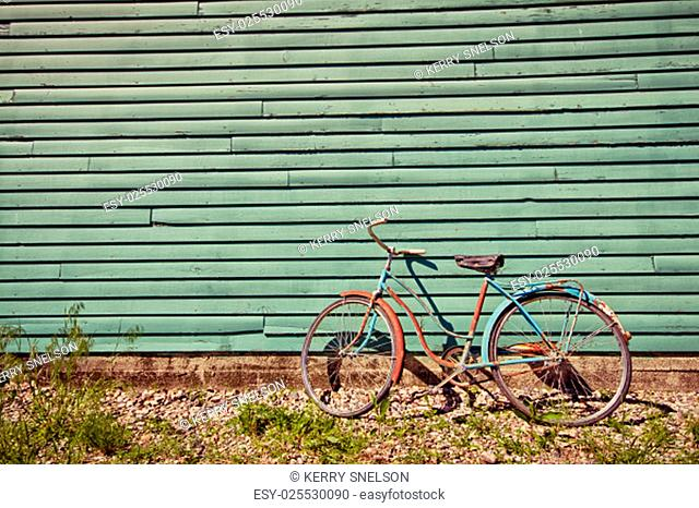 Abandoned bike leaning against a green wall