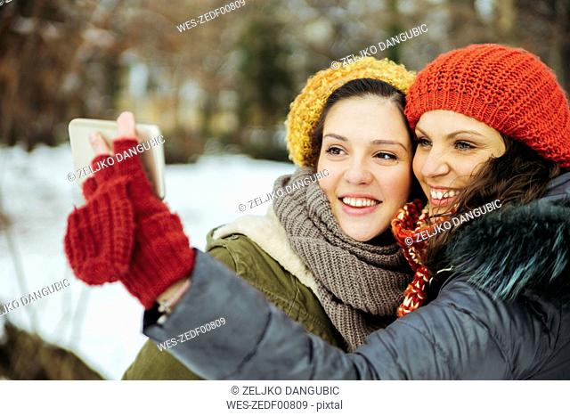 Two friends taking selfies in the snow