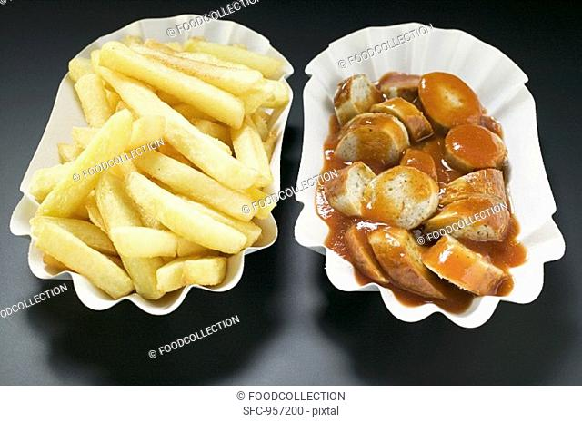 Sausage with ketchup and chips in paper dishes