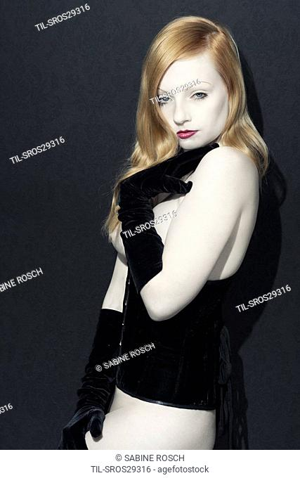 Pale red head girl facing camera wearing black lace veil and corset