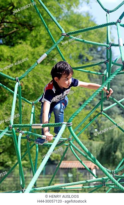 Child playing on a spiderweb, France