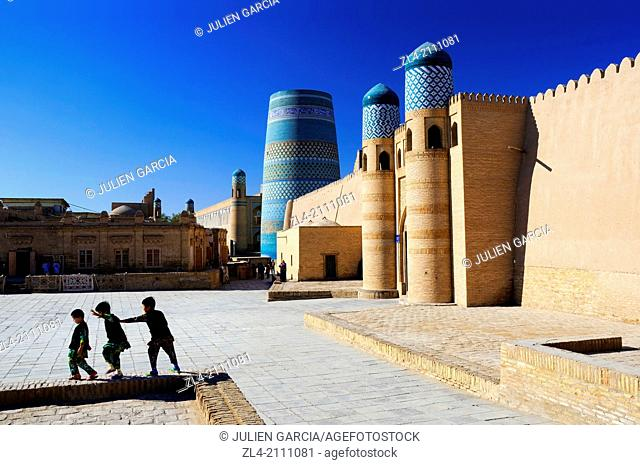Children playing near the Kuhna Ark fortress and the unfinished minaret Kalta Minor. Uzbekistan, Khorezm, Khiva, Itchan Kala (inner town)