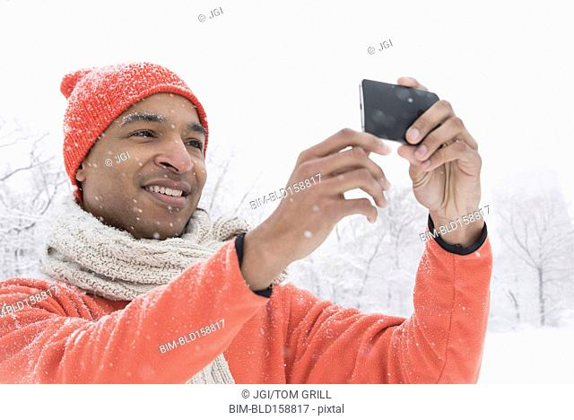 Black man using cell phone in snow
