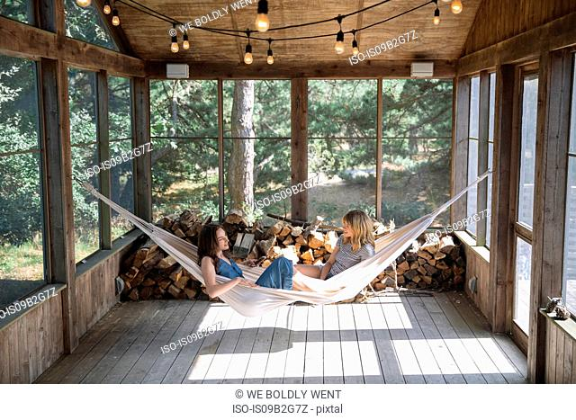 Women relaxing and chatting in hammock, Amagansett, New York, USA