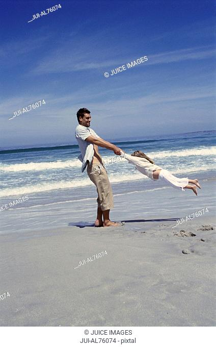 View of a father swinging his daughter around by her arms on the beach