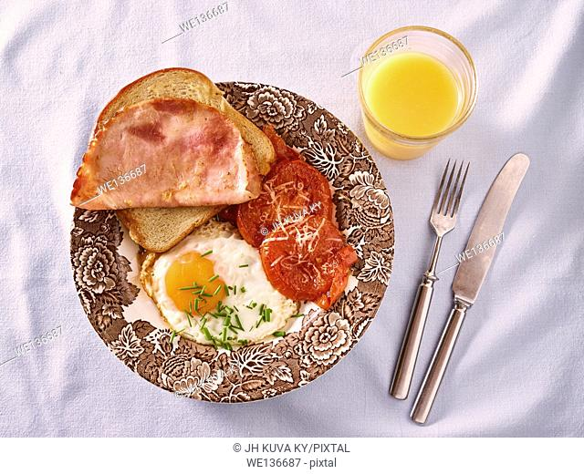Breakfast, fried egg, tomatoes and bread with a ham