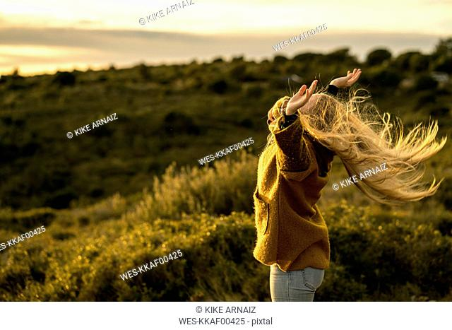 Young woman standing in nature raising her arms