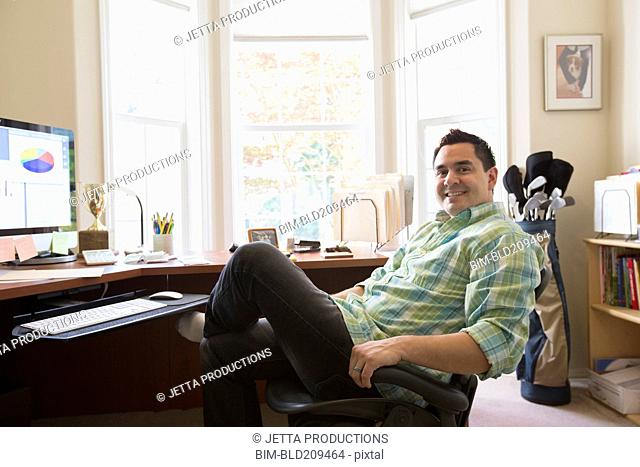 Pacific Islander businessman smiling at desk