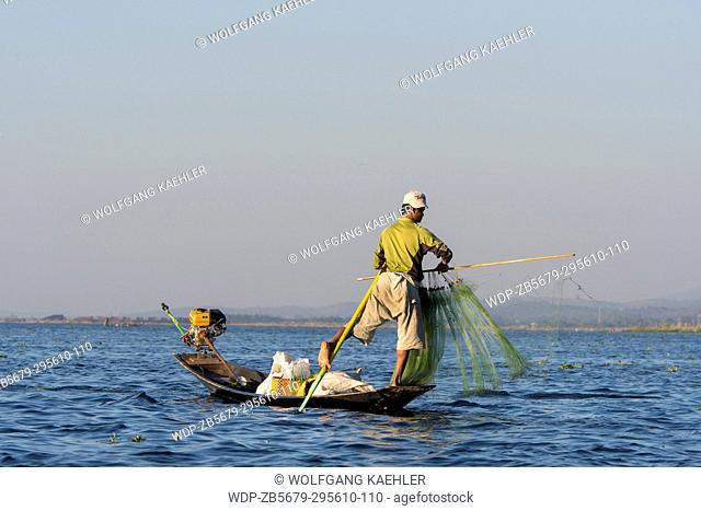 A leg-rowing fisherman in his boat is setting fishing net on Inle Lake in Myanmar