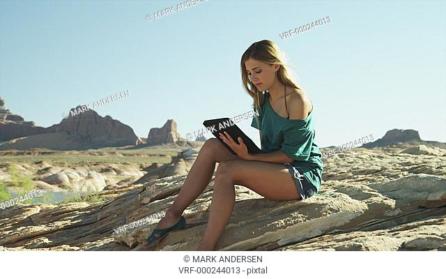 WS DS Young woman using ipad in desert landscape / Lake Powell, Utah, USA