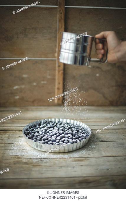 Hand sprinkling powder sugar over blueberries