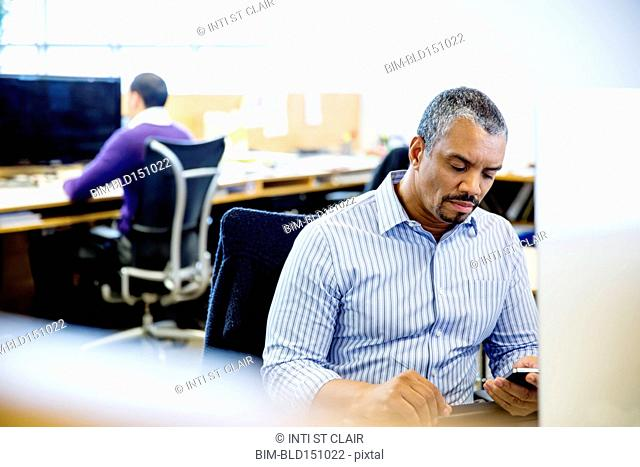 Businessman using cell phone at office desk