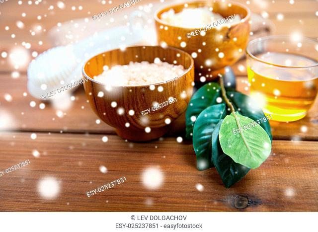 beauty, spa, bodycare, natural cosmetics and bath concept - himalayan pink salt and body scrub with brush on wooden table over snow