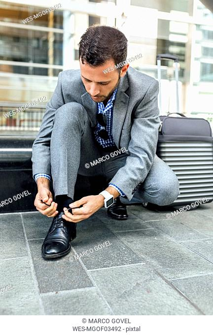 Businessman tying his shoes in the city