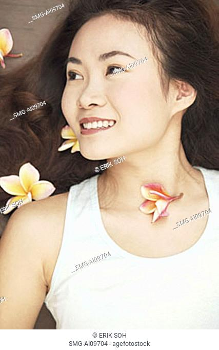 Young woman lying down, flowers in hair