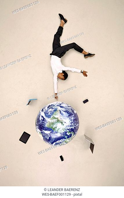 Businesswoman balancing globe with mobile devices on fingertip