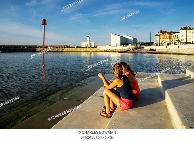 Teenage girls sitting on steps along the waterfront; Margate, Kent, England