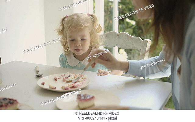 Mother feeding cake to her daughter at dining table