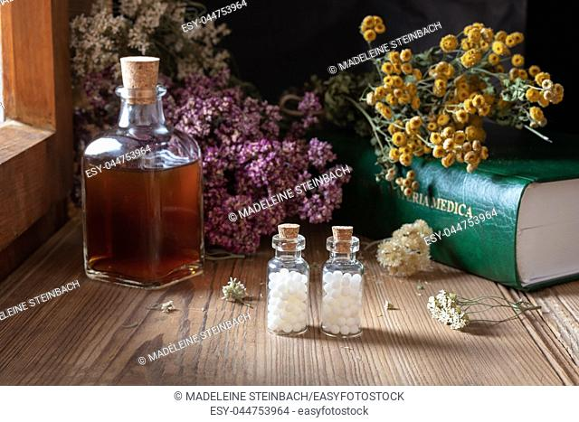 Two bottles of homeopathic globules with dried herbs and a materia medica, i. e. a list of remedies and their therapeutic properties