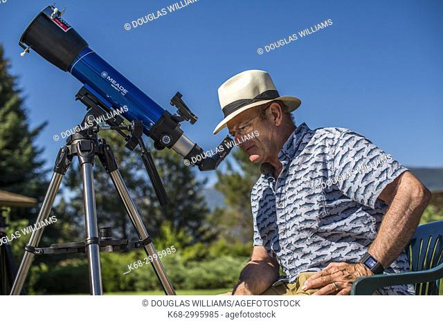 Man looking at solar eclipse with telescope