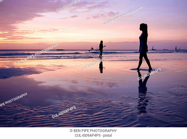 Silhouetted young woman strolling on beach at sunset, Boracay Island, Visayas, Philippines