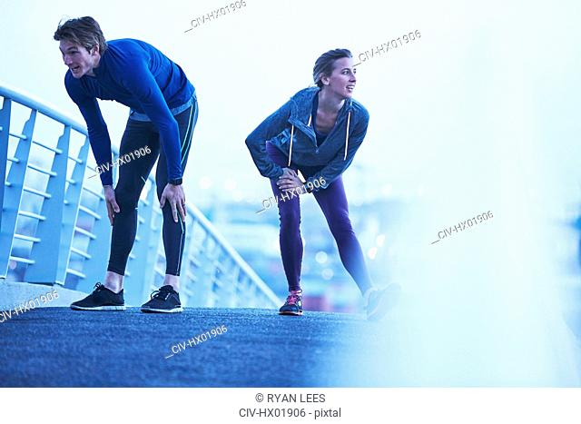 Runner couple stretching legs on footbridge