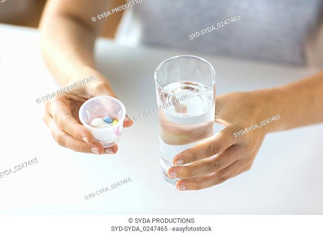 close up of hands with pills and glass of water