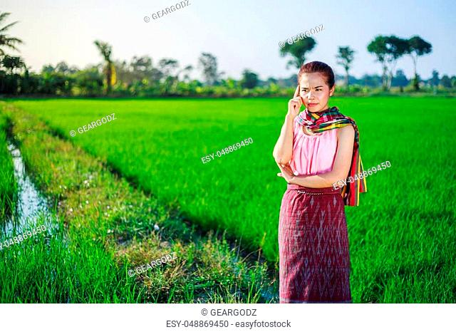 beautiful farmer woman thinking in rice field, Thailand