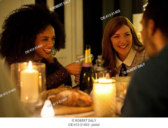 Smiling friends drinking champagne at candlelight dinner table