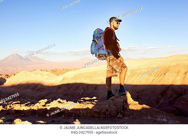 Atacama, Chile-september 14, 2014: A mature caucasian hiker with his backpack on the peak of montain watching the sunset on Atacama desert in Chile