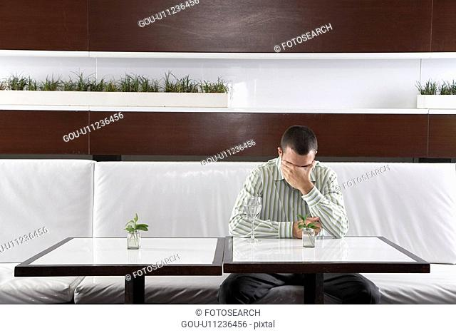 Stressed businessman leaning on hand in restaurant