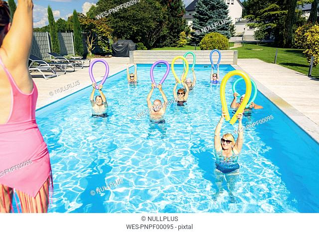 Group of seniors with trainer doing water gymnastics in pool