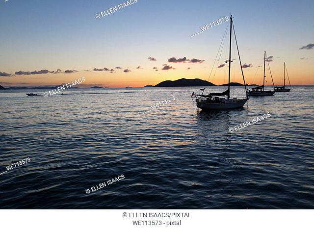 Silhouette of sailboats moored in water and power boat riding by in the orange glow of sunset in the Caribbean