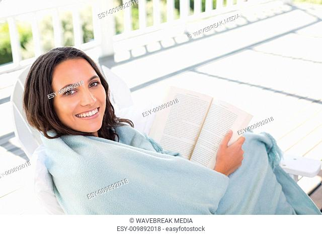 Pretty brunette sitting on a chair and reading a book