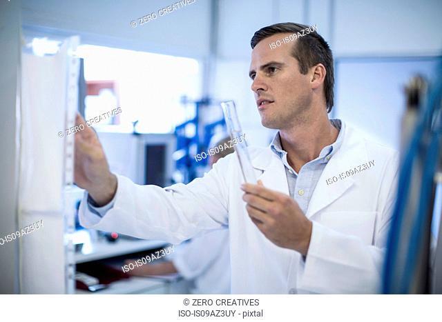 Mid adult man adjusting laboratory equipment, holding test tube