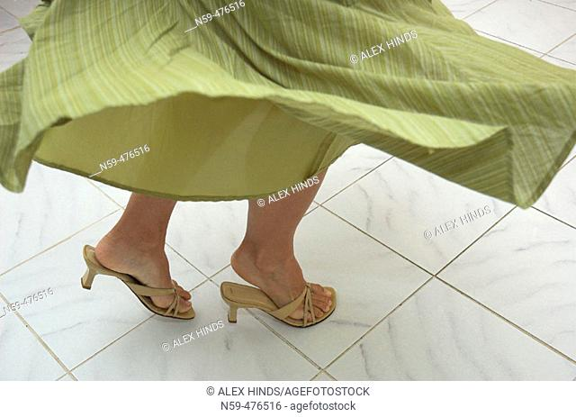 Young woman's legs in a dance motion on tile floor