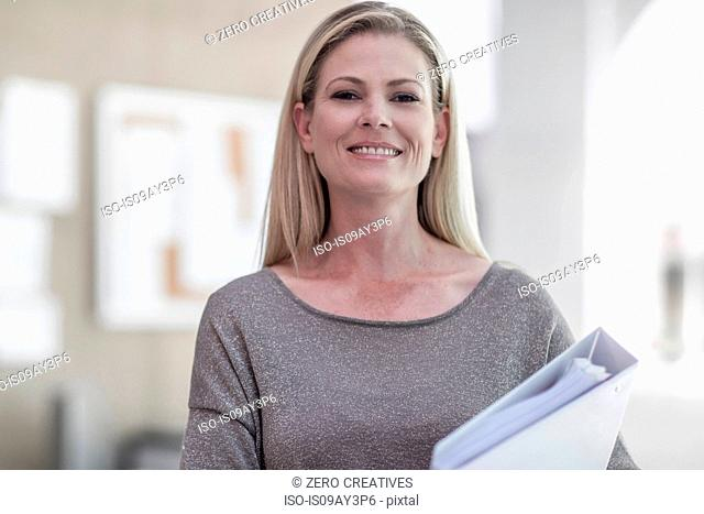 Portrait of female designer carrying file in design studio