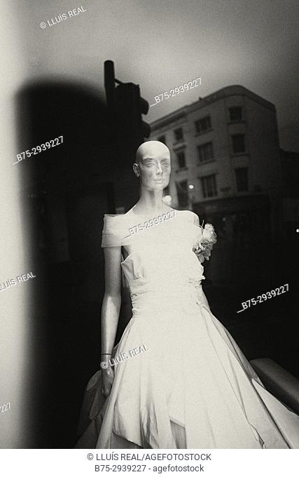 Shop window with mannequin in wedding dress. Reflection of building in glass. London, England