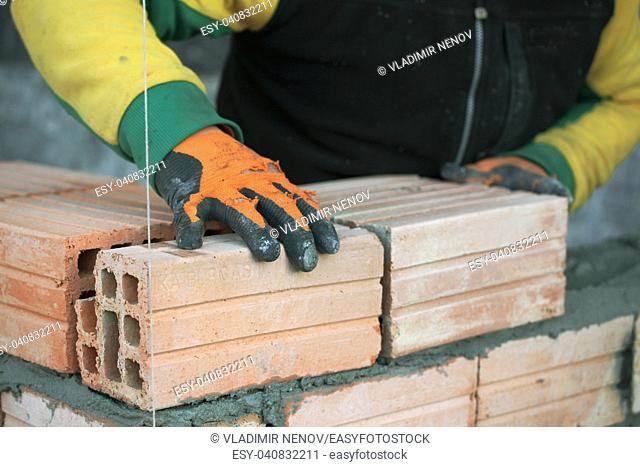 Industrial bricklayer installing bricks on construction site