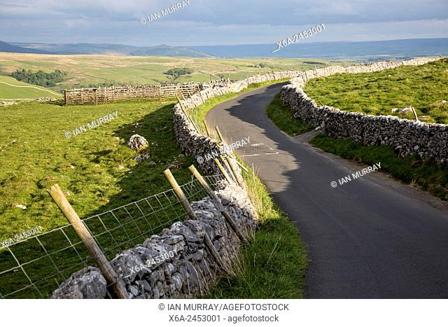 Country lane and dry stonewalls, Malham, Yorkshire Dales national park, England, UK