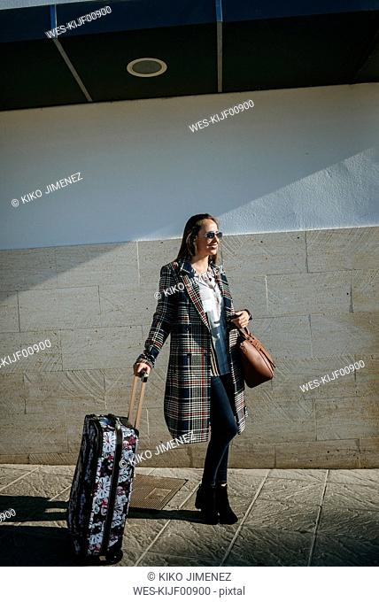 Smiling woman waiting with suitcase