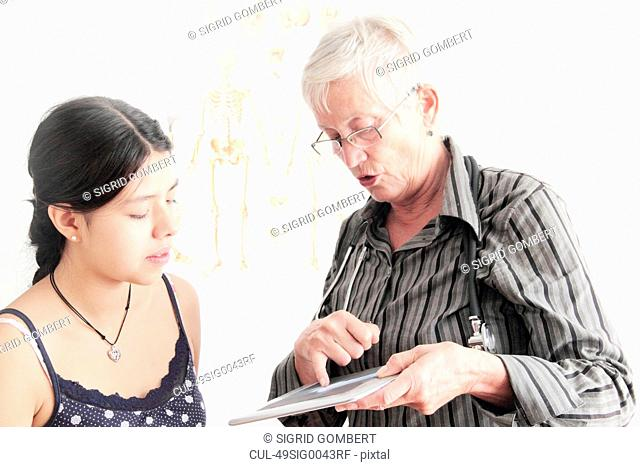 Doctor showing x-ray to teenage girl